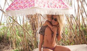 girl and baby under luxury beach umbrella