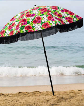 Red flowered beach umbrella on the beach with fringe
