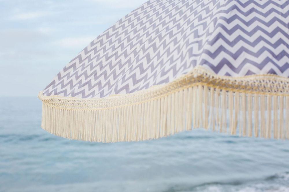 Fringed gray and white beach umbrella