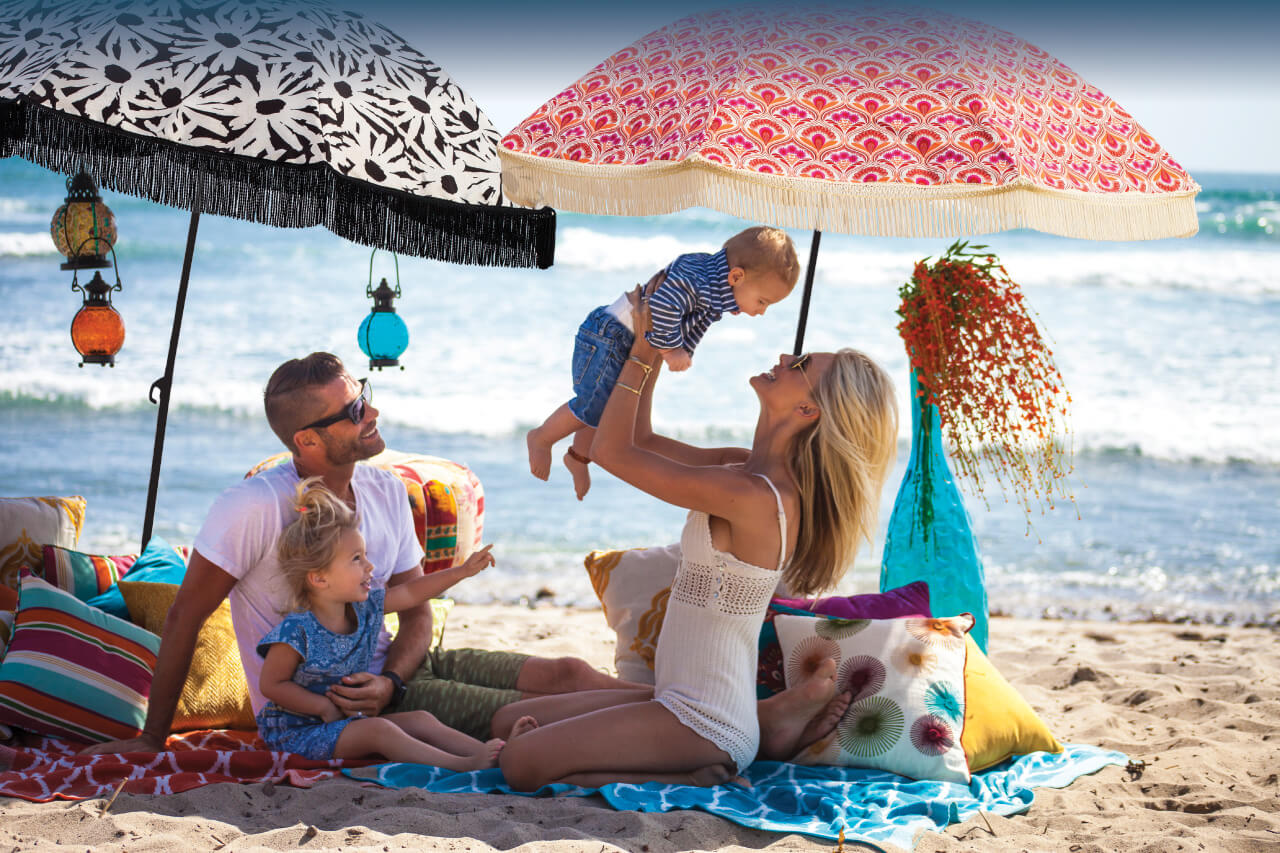 Family fun shaded from the sun with beach umbrellas by Beachbrella.com