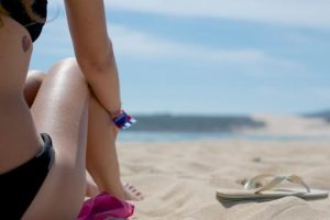 close up of girl sitting on the sand