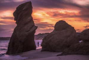 A beach with two very large rocks reaching towards the sky with an orange and purple sunset overhead.