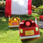 Cardboard cars in front of outdoor movie projection screen in backyard for family fun