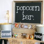 Backyard popcorn bar equipped with big buckets of popcorn along with fun toppings for family to choose from
