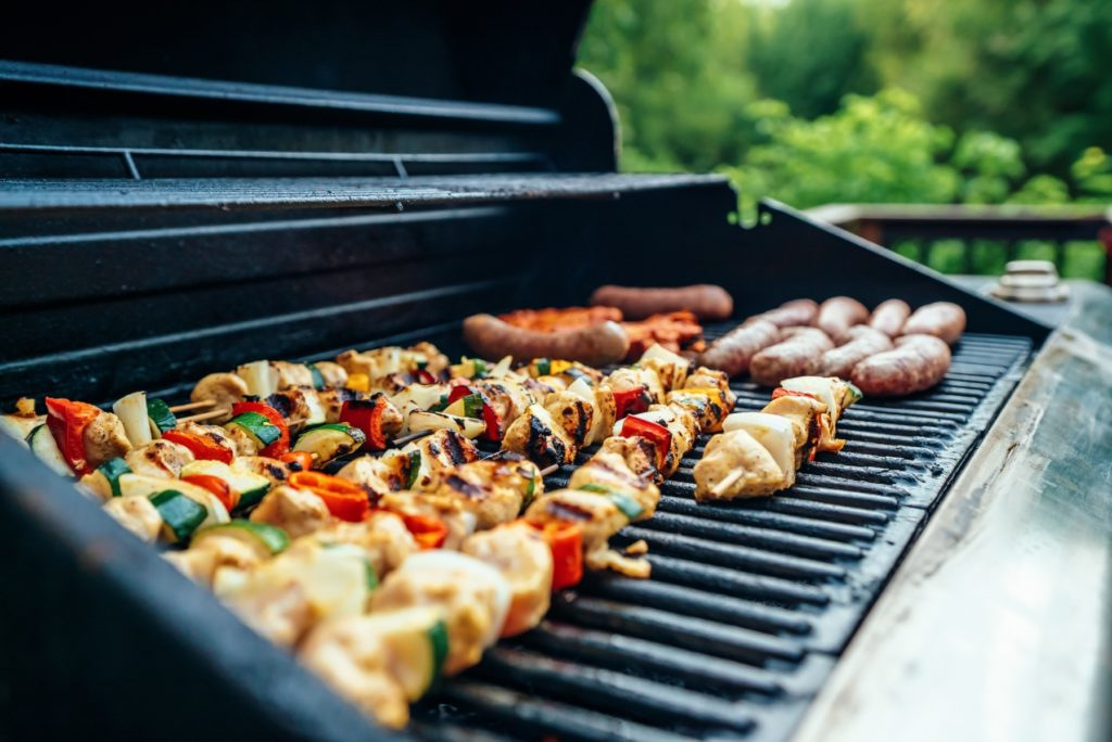 Close up of grill with kabobs and hot dogs grilling on it