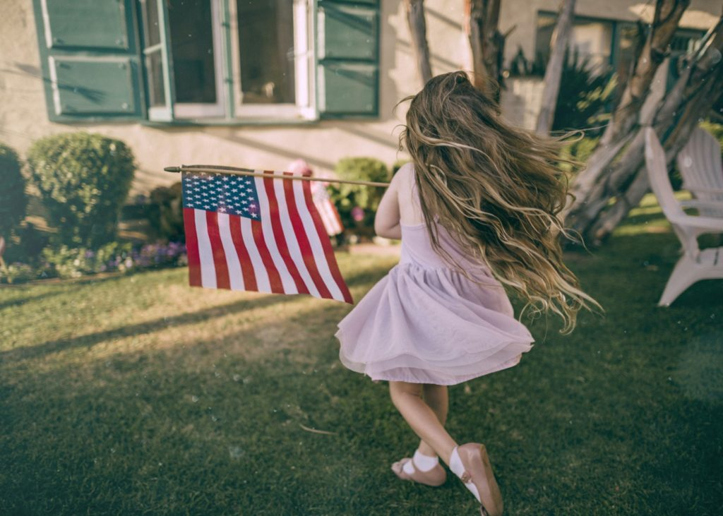 Little girl having fun and running with American flag