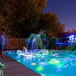 Family backyard pool at night with fun submerged glow sticks